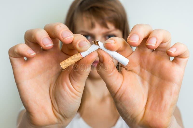 Frau mit defekter Zigarette - hören Sie auf, Konzept zu rauchen stockfotos