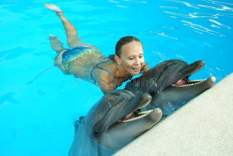 Frau mit Delphinen im Wasser stockbilder