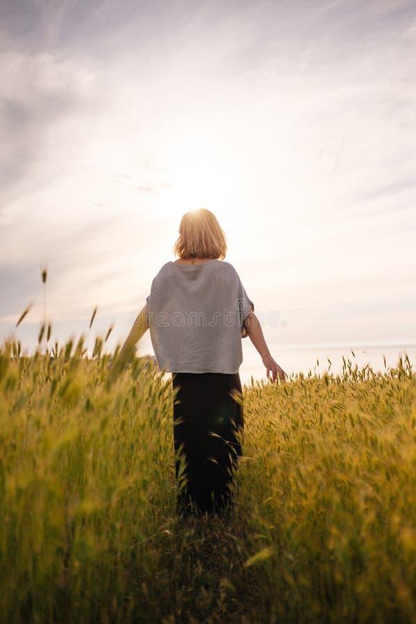Frau mit dem Arme ausgestreckten Gehen zur Sonne auf einem Weizengebiet Glücklich, ruhig, ruhig, harmonisch, frei, offen lizenzfreie stockbilder