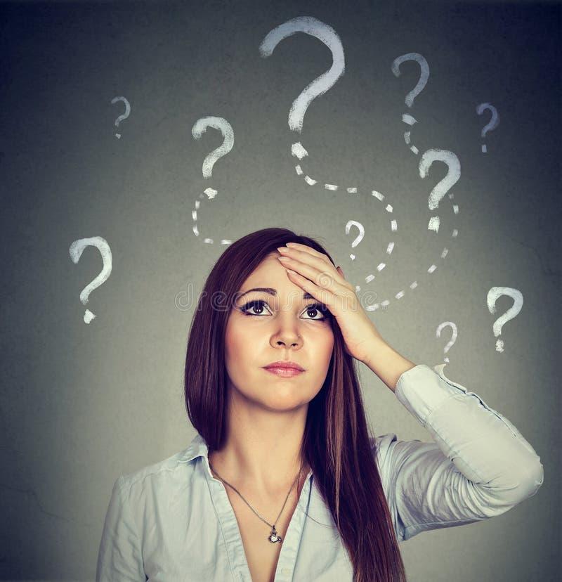 Frau mit dem besorgten Gesichtsausdruck, der oben schaut, hat viele Fragen stockbilder