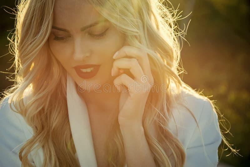 Frau mit dem blonden Haar sprechen über bewegliche, neue Technologie stockfoto