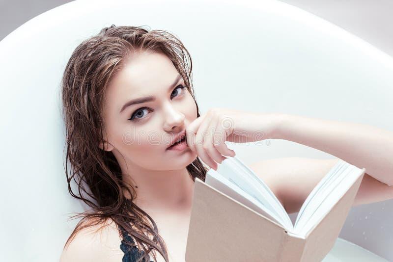 Frau mit dem Buch, das im Bad liegt stockfotos