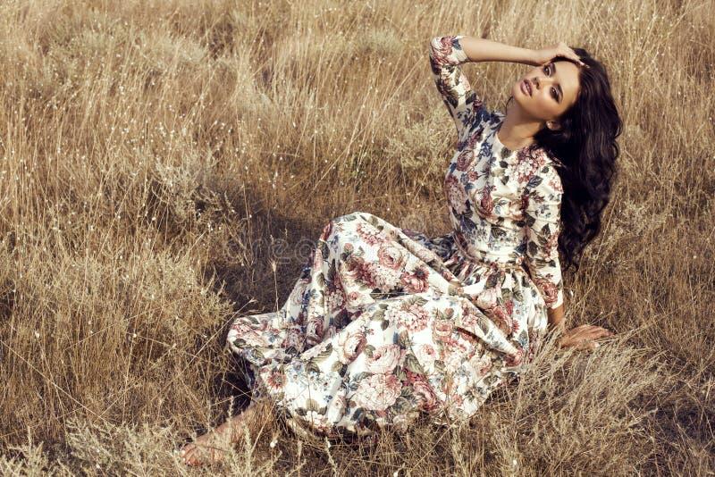 Frau mit dem dunklen Haar trägt das luxuriöse bunte Kleid, das auf dem Sommergebiet aufwirft lizenzfreie stockfotos