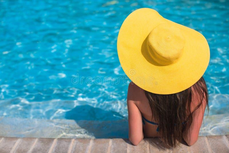 Frau mit dem gelben Hut, der sich herein am Swimmingpool entspannt stockfoto