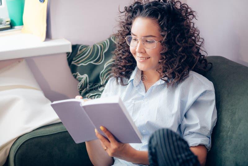 Frau mit dem gelockten Haar im zufälligen clothers Lesebuch zu Hause lizenzfreie stockbilder