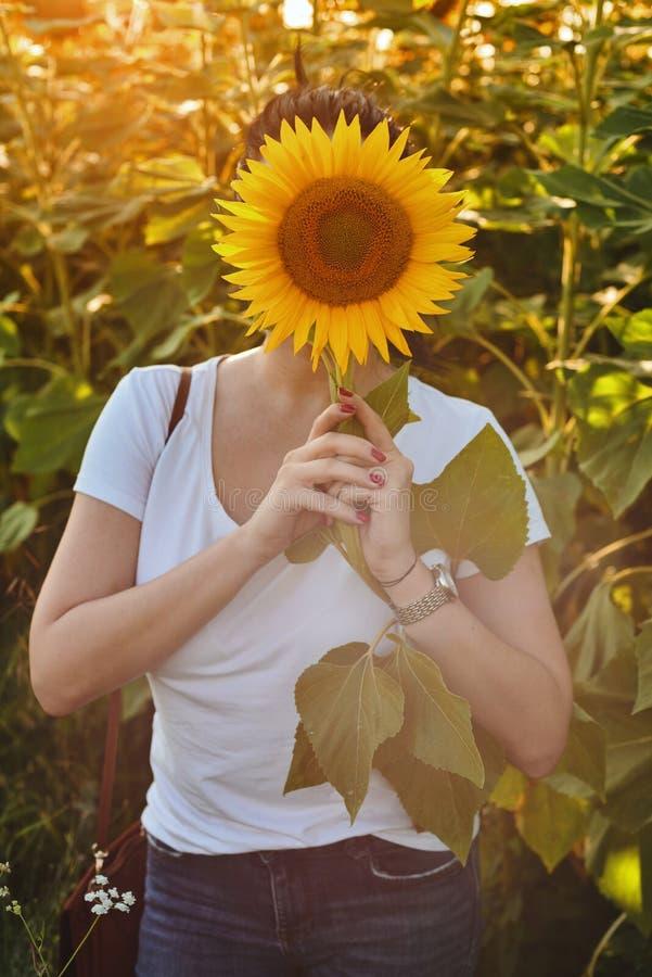 Frau mit dem Gesicht bedeckt mit Sonnenblume stockbild