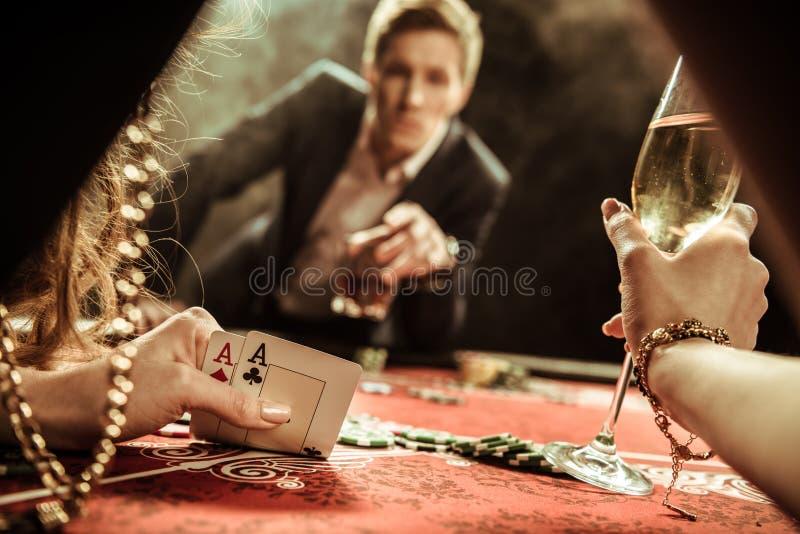 Frau mit dem Getränk, das Karten beim Spielen des Pokers betrachtet stockfotografie