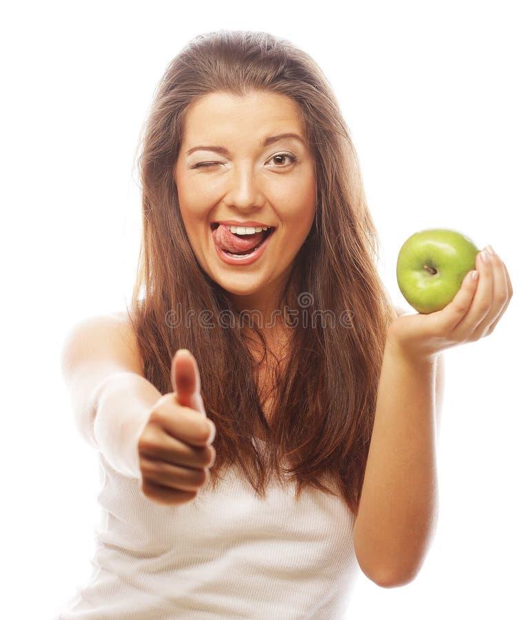 Frau mit dem grünen Apfel- und sich zeigendaumen lizenzfreie stockbilder