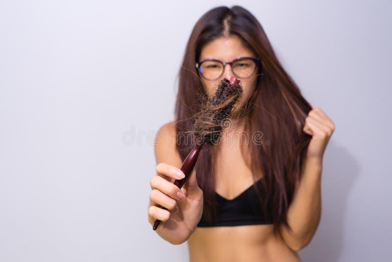 Frau mit dem Haarausfall, der Kamm hält Verlierendes probl Haar des jungen Mädchens lizenzfreie stockfotos