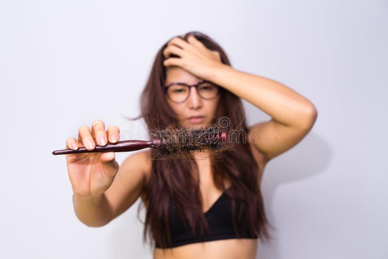 Frau mit dem Haarausfall, der Kamm hält Verlierendes probl Haar des jungen Mädchens stockfoto