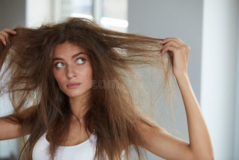 Frau mit dem Halten des lang schädigenden trockenen Haares Haar-Schaden, Haarpflege stockbild