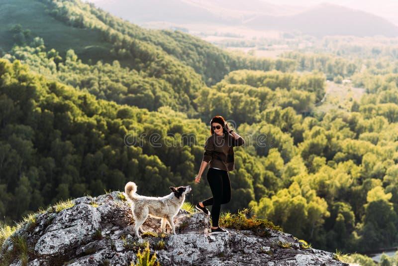 Frau mit dem Hund, der in die Berge geht Hunde- Freund Gehen mit Ihrem Haustier Reisen mit einem Hund Ein Haustier Intelligenter  stockfotografie