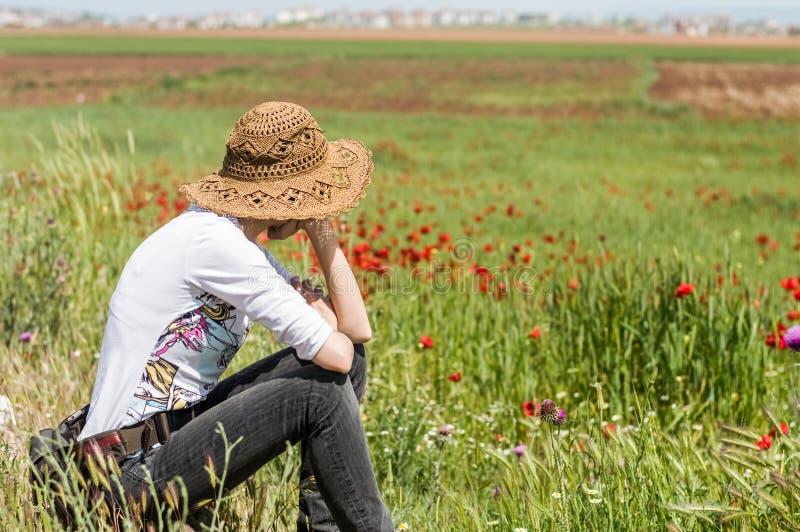 Frau mit dem Hut, der voll in einer Wiese von Blumen, die Natur genießend sitzt stockfotografie