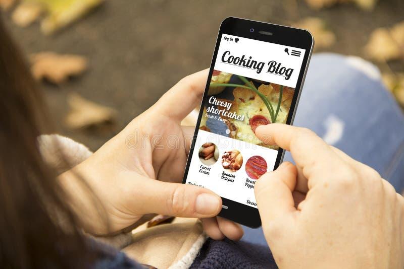 Frau mit dem Kochen des Blogtelefons im Park stockbilder