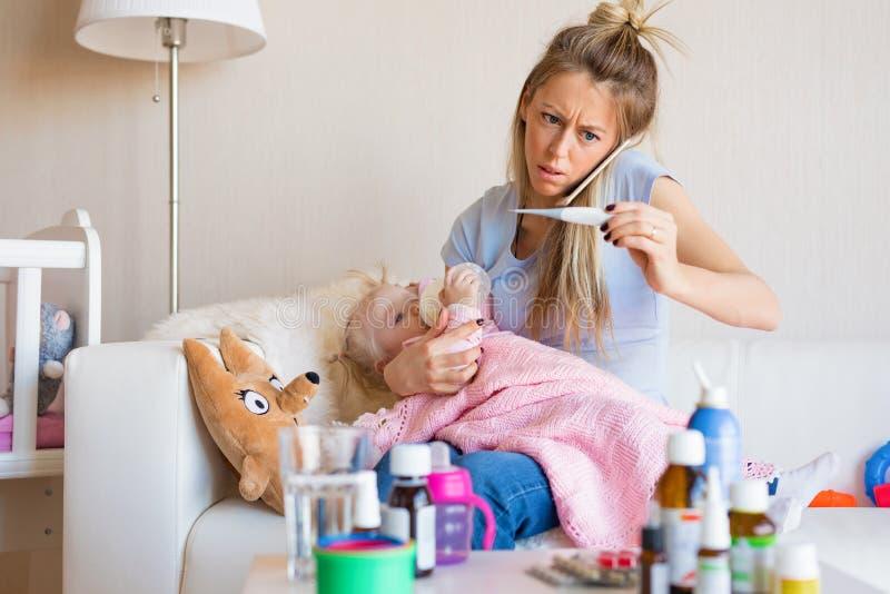 Frau mit dem kranken Baby, das Doktor anruft lizenzfreie stockbilder