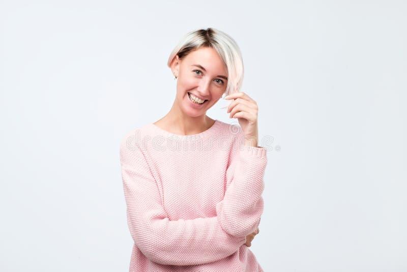 Frau mit dem kurzen gefärbten Haar, das sehr frohes Lächeln mit dem breiten Lächeln zeigt ihre perfekten Zähne ist stockfotografie