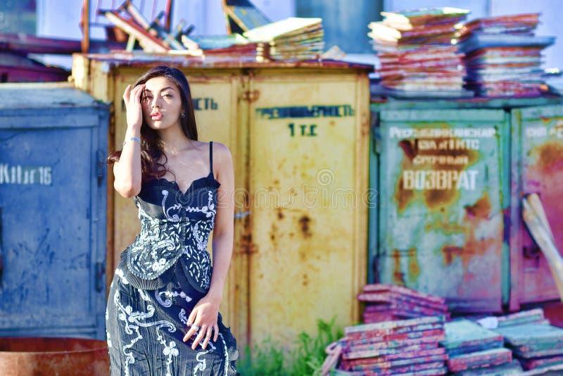 Frau mit dem lang flüssigen braunen Haar, das auf einem Hintergrund von verlassenen Lagern aufwirft stockbilder