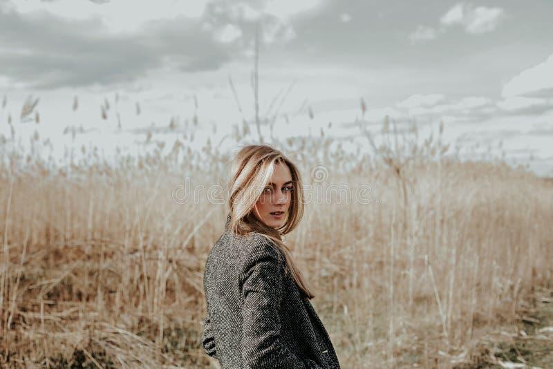 Frau mit dem langen blonden Haar kleidete im Wollmantel an, der Kamera über ihrer Schulter betrachtet lizenzfreies stockfoto