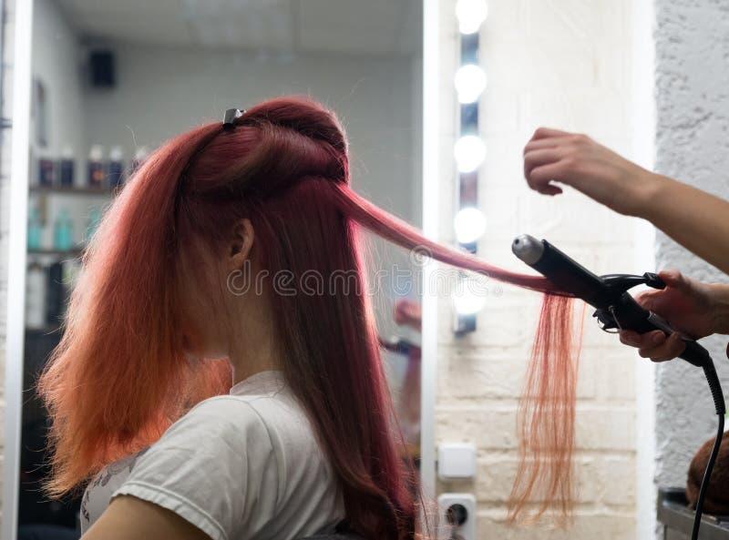 Frau mit dem langen Haar, das auf den Windenverfahrenslocken unter Verwendung der Brennscheren im Salonfriseur sitzt lizenzfreie stockfotos