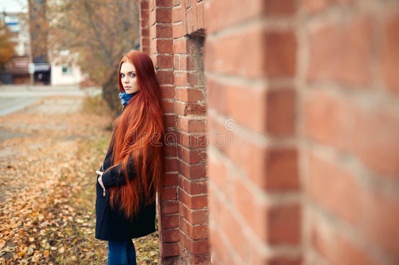 Frau mit dem langen roten Haar geht in Herbst auf der Straße Mysteriöser träumerischer Blick und das Bild des Mädchens Rothaarige stockfotografie