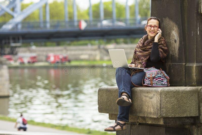 Frau mit dem Laptop, der auf dem Damm des Flusses in der alten Stadt sprechend an einem Handy sitzt stockfoto