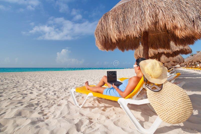 Frau mit dem Laptop, der auf dem deckchair sich entspannt lizenzfreie stockfotografie