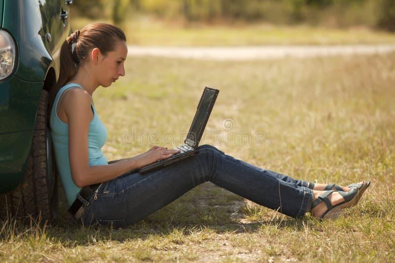 Frau mit dem Laptop, der draußen arbeitet lizenzfreie stockfotos