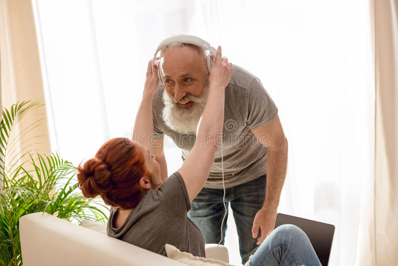 Frau mit dem Laptop, der Kopfhörer auf bärtigen Mann justiert stockbild