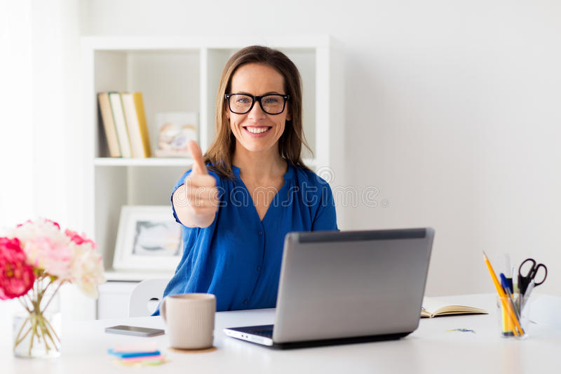 Frau mit dem Laptop, der sich Daumen im Büro zeigt lizenzfreies stockfoto