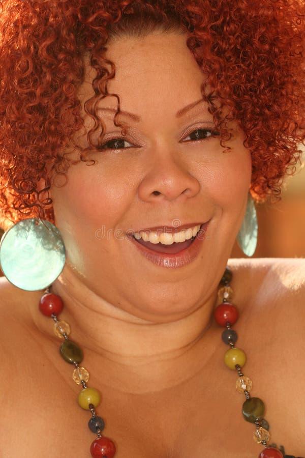 Frau mit dem lockigen roten Haar und den hellen Schmucksachen lizenzfreies stockbild