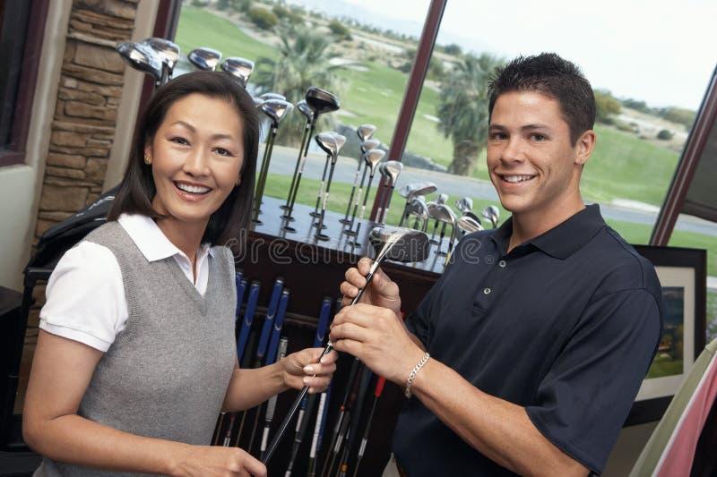 Frau mit dem Mann, der Golfclub vorwählt lizenzfreie stockfotos