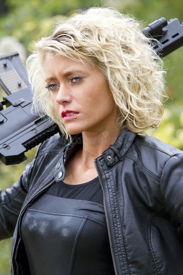 Frau mit dem Maschinengewehr im Freien stockbild