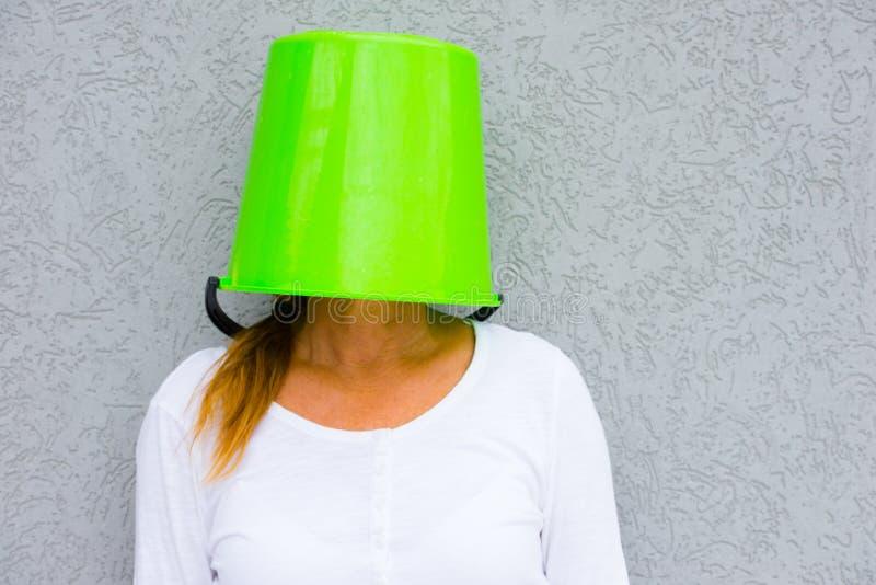 Frau mit dem obenliegenden Verstecken des Eimers stockfoto
