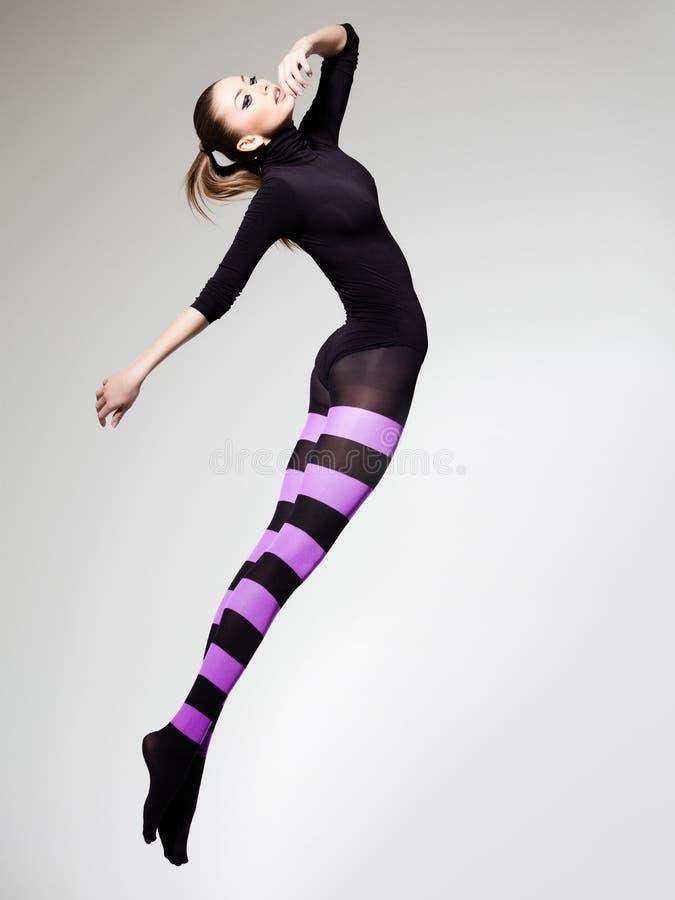 Frau mit dem perfektem Karosserienspringen kleidete in den purpurroten gestreiften Strumpfhosen und in der schwarzen Spitze an stockbilder