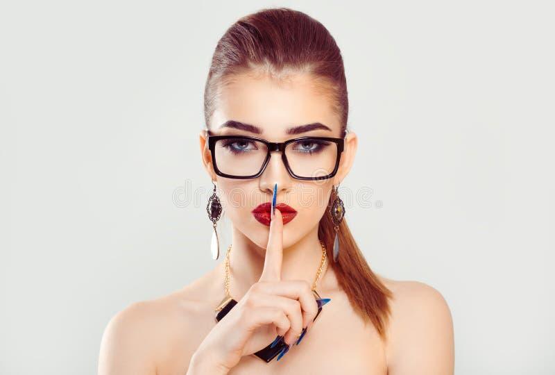 Frau mit dem rötlich braunen Haar zeigt die anderen, um ruhig zu bleiben, um das Geheimnis zu halten lizenzfreies stockbild
