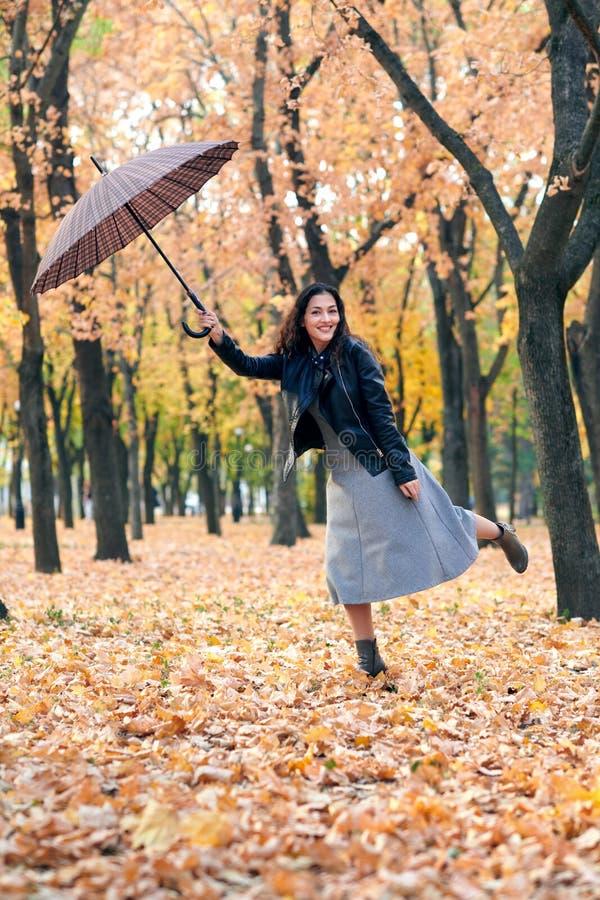 Frau mit dem Regenschirm, der im Herbstpark aufwirft Helle gelbe Blätter und Bäume Sie ahmt den Wind nach stockfotografie