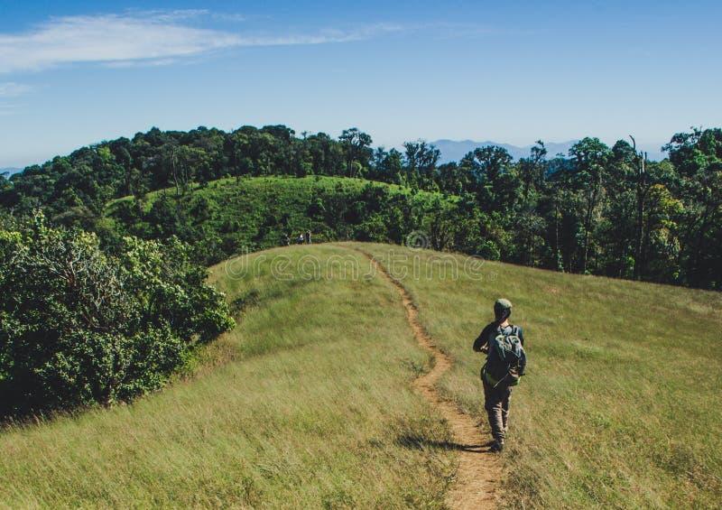 Frau mit dem Rucksack, der auf den Bergen, Reise-Lebensstilerfolgskonzept wandert stockbild