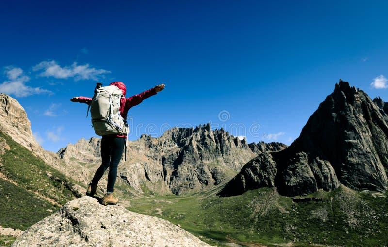 Frau mit dem Rucksack, der auf die Oberseite der großen Höhe Gebirgswandert lizenzfreie stockfotos