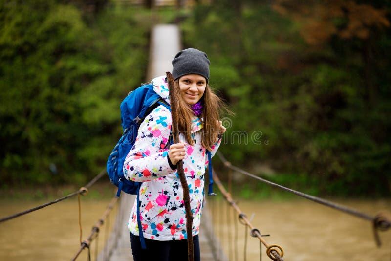 Frau mit dem Rucksack, der Lebensstilabenteuer-Konzeptwald und Querfluß in Waldaktive Ferien wandert lizenzfreies stockbild