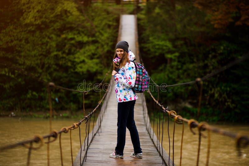 Frau mit dem Rucksack, der Lebensstilabenteuer-Konzeptwald und Querfluß in Waldaktive Ferien wandert lizenzfreie stockfotos