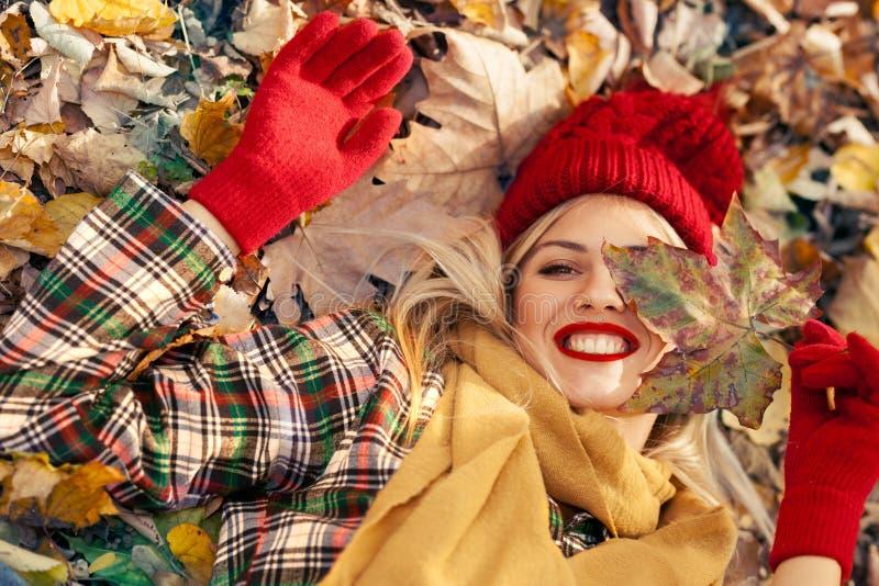 Frau mit dem schönen Lächeln, das mit Blatt beim Lügen auf dem Boden spielt lizenzfreies stockbild