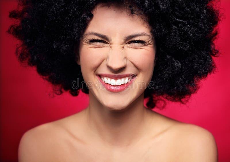 Frau mit dem schwarzen Afrofrisurlächeln stockfotografie