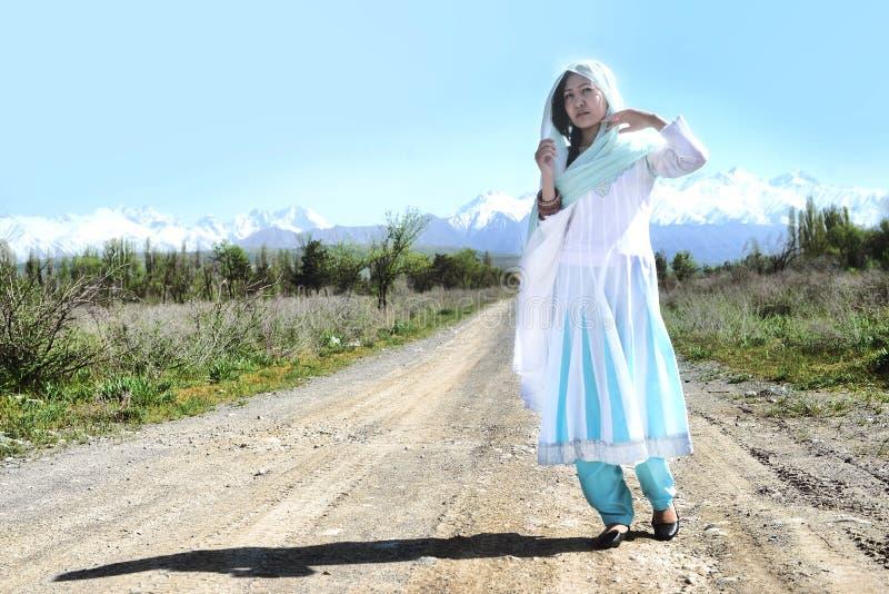 Frau mit dem schwarzen Haar im blauen Sari, auf der rular Straße, Natur stockbild