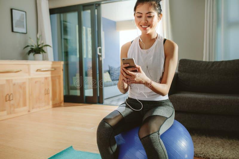 Frau mit dem Smartphone, der auf einem Eignungsball sich entspannt lizenzfreie stockbilder