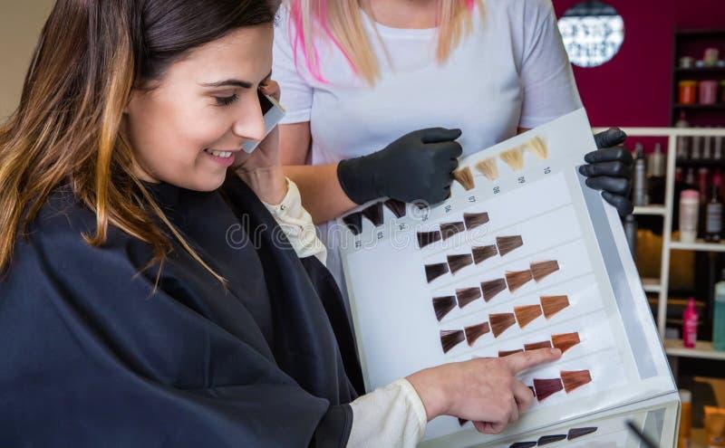Frau mit dem Smartphone, der eine Haarfärbemittelpalette schaut lizenzfreie stockbilder