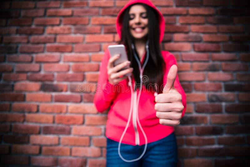 Frau mit dem Smartphone, der sich Daumen zeigt lizenzfreies stockbild