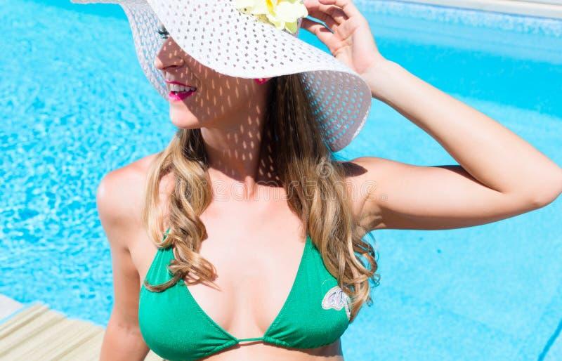 Frau mit dem Sonnenhut, der am Swimmingpool sich entspannt lizenzfreies stockfoto