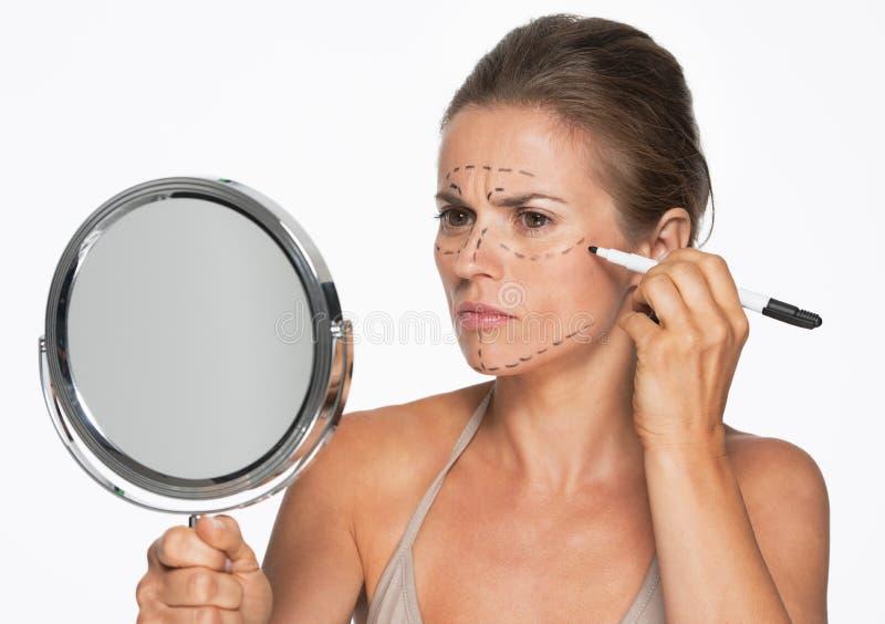 Frau mit dem Spiegel, der Kennzeichen der plastischen Chirurgie auf Gesicht macht stockfoto