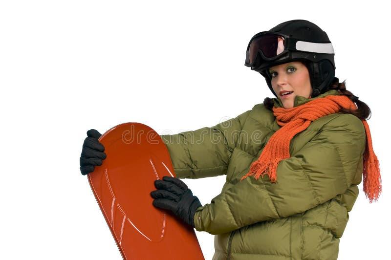Frau mit dem Sturzhelm, der orange Snowboard anhält stockfotos
