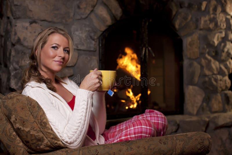 Frau mit dem Tee, der durch Fireplace sitzt lizenzfreie stockfotografie